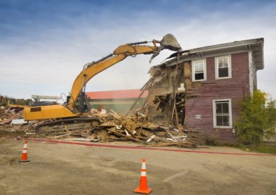 A digger demolishing a house for reconstruction.